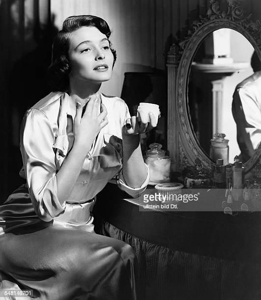 Young woman applying a lotion on her neck 1955 Vintage property of ullstein bild