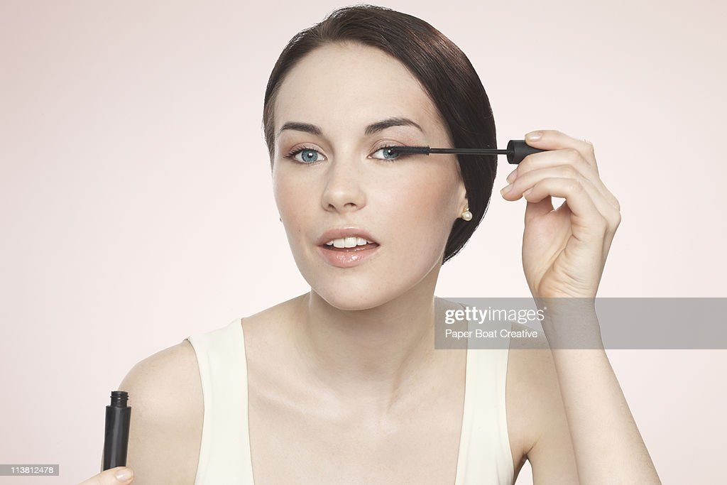 Young woman applying black mascara