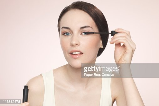 Young woman applying black mascara : Stock Photo