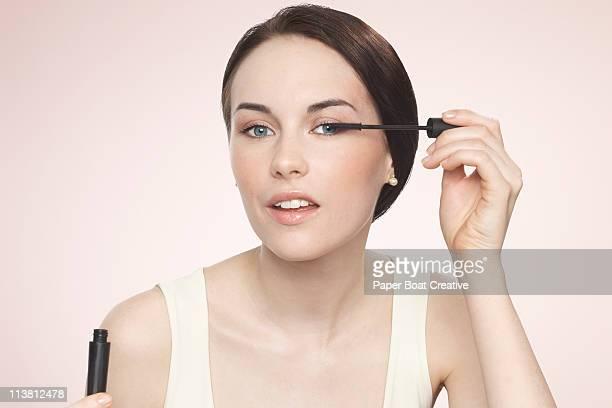 Young woman applying black mascara