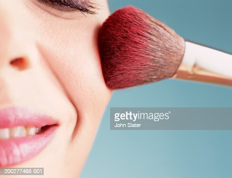 Young woman applying blusher, close-up of cheek