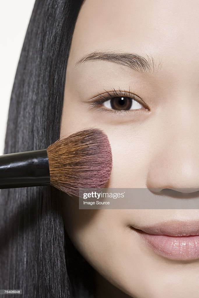 Young woman applying blusher : Stock Photo