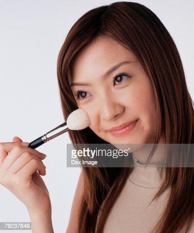 Young woman applying brusher : Stock Photo