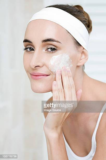 Young woman applying cleanser