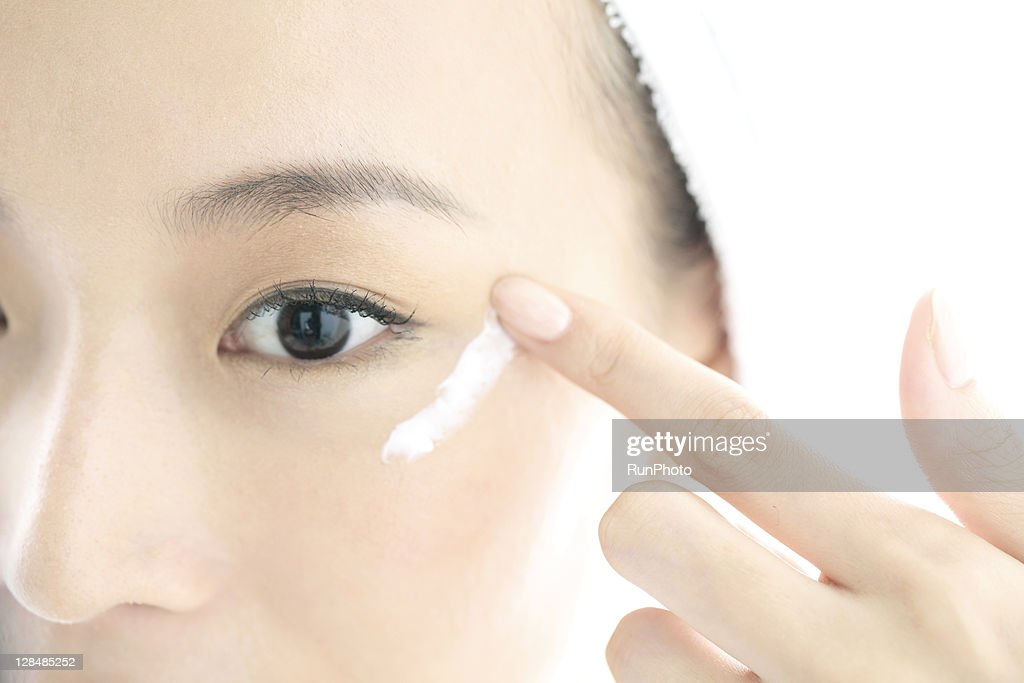 young woman applying cream on face : Stock Photo