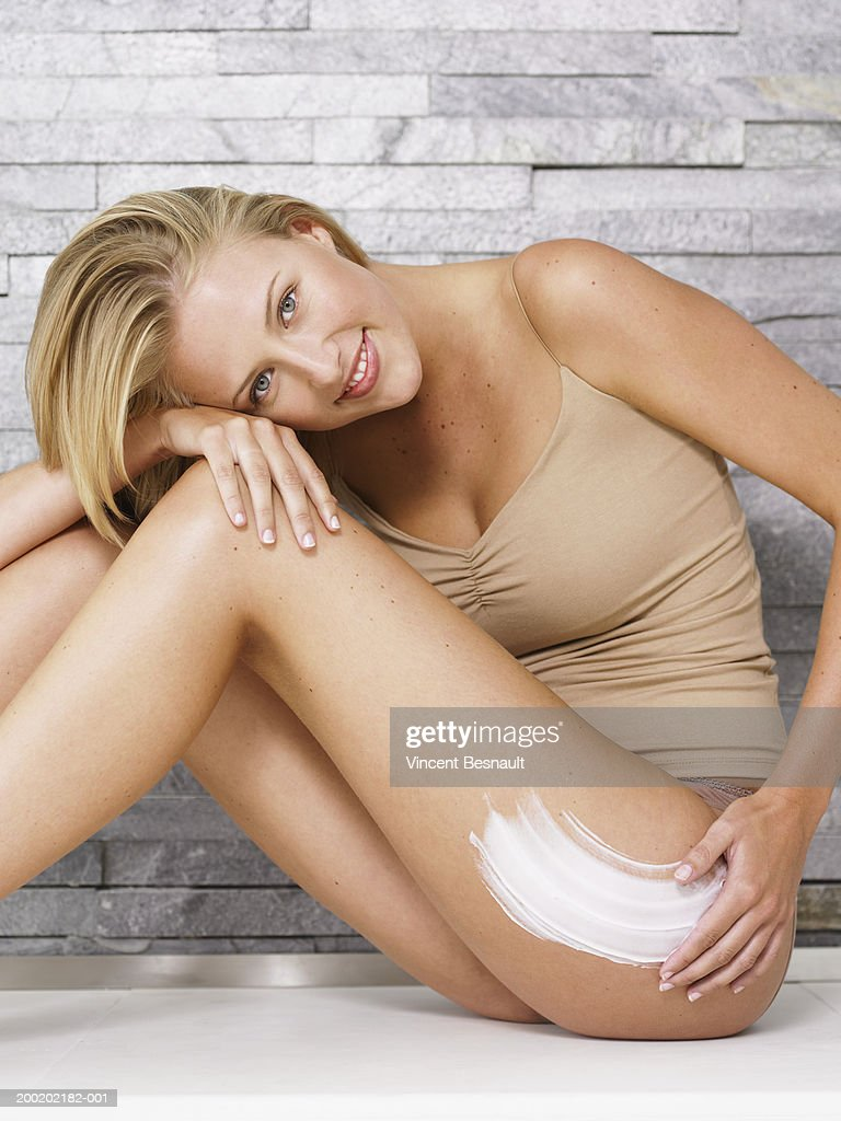 Young woman applying cream to leg, resting head on knee, portrait : Stock Photo