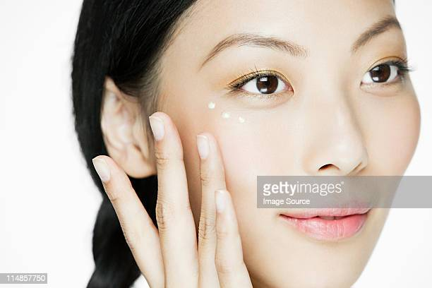 Young woman applying eye cream
