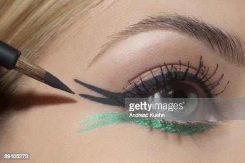 Young woman applying eye make up, close up.