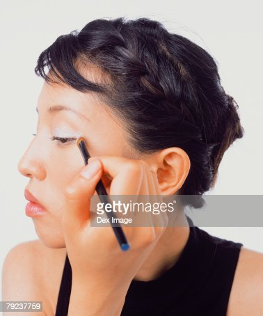 Young woman applying eye shadow : Stock Photo