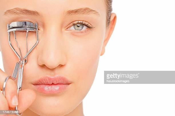 how to use eyelash curler. young woman applying eyelash curler how to use n