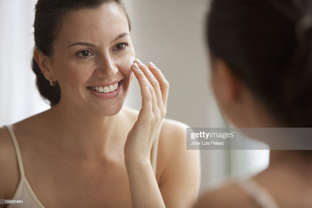 Young woman applying facial cream : Stock Photo