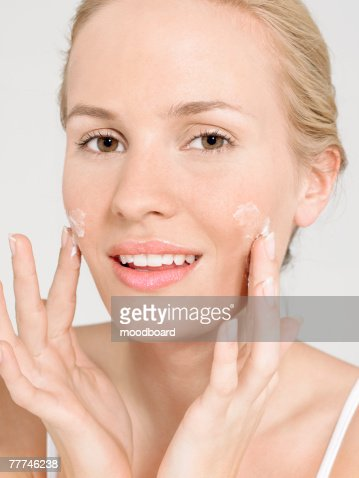 Young Woman Applying Facial Cream : ストックフォト