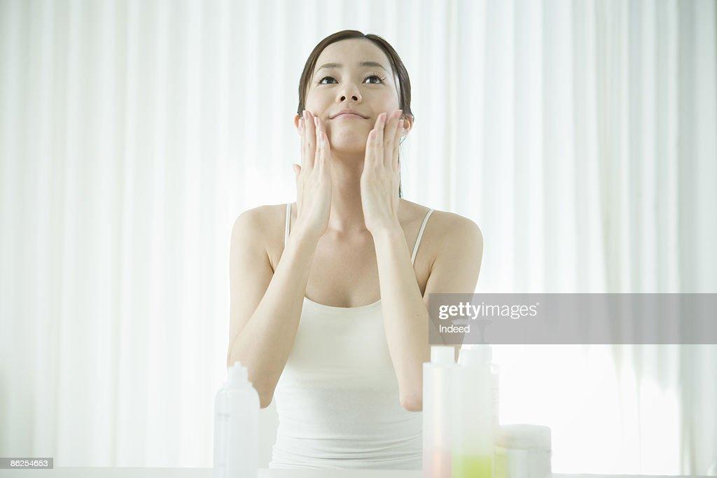 Young woman applying facial cream : Stock Photo