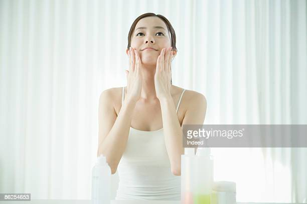 Young woman applying facial cream
