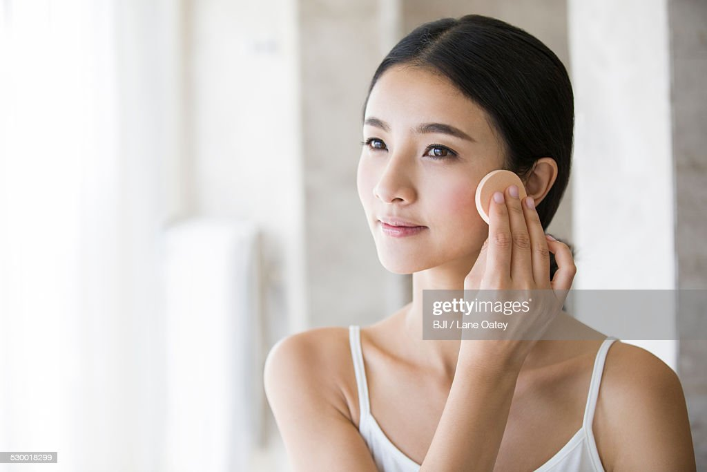 Young woman applying facial powder