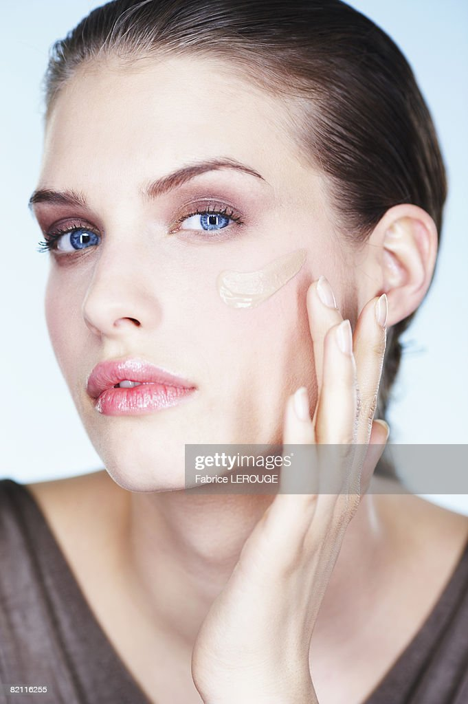 Young woman applying foundation