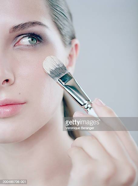 Young woman applying foundation to cheek with make-up brush, close-up