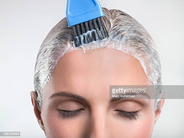 Young woman applying hair color