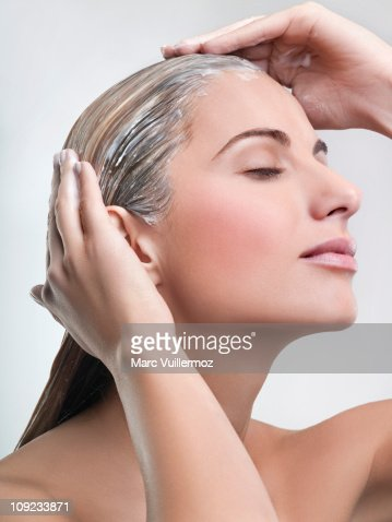 Young woman applying hair mask