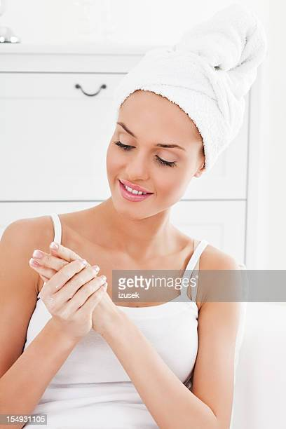 Young woman applying hand cream