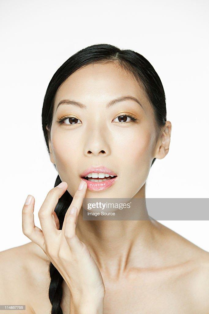 Young woman applying lipgloss : Stock Photo