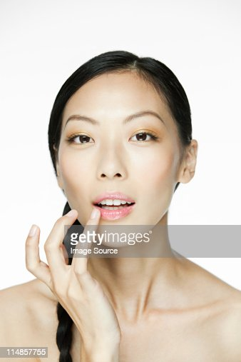 Young woman applying lipgloss : Stock Photo