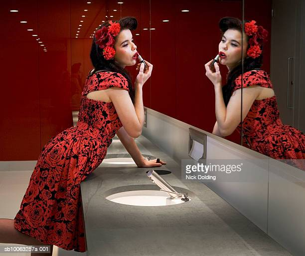 Young woman applying lipstick in mirror of public lavatory, side view