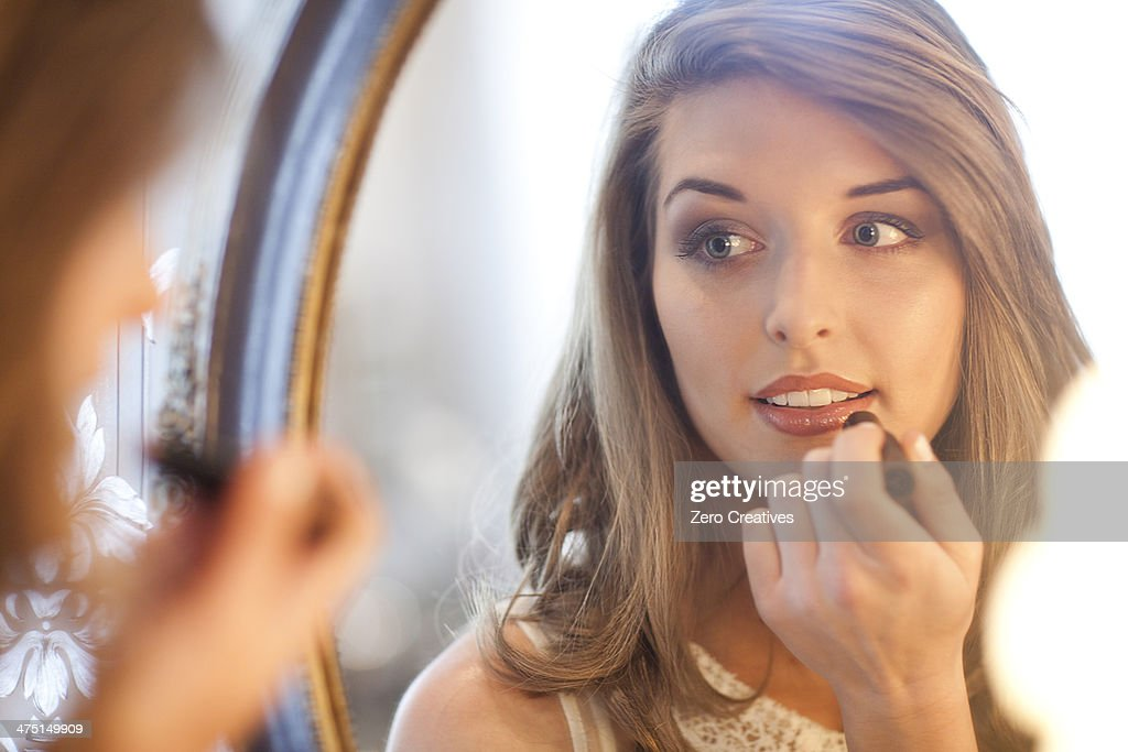 Young woman applying lipstick in mirror : ストックフォト