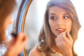 Young woman applying lipstick in mirror