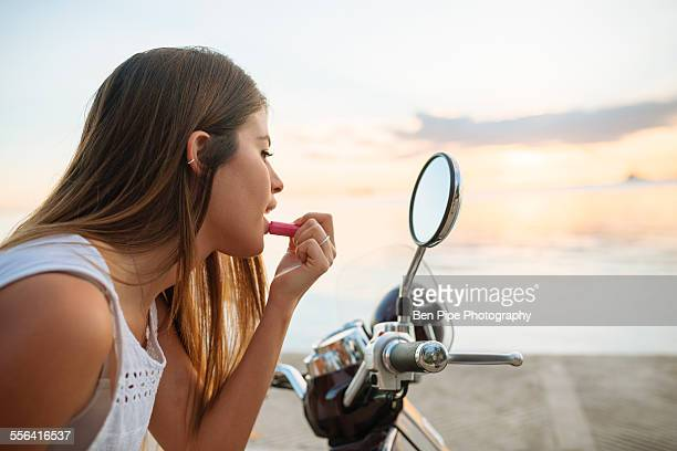 Young woman applying lipstick in motorcycle wing mirror, Manila, Philippines