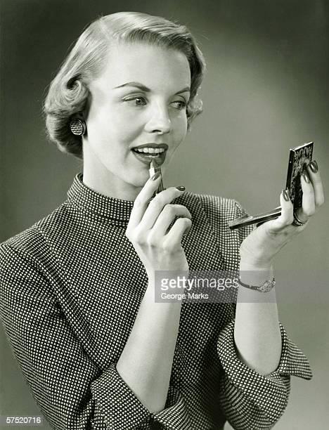 Young woman applying lipstick, looking at powder compact mirror, (B&W), close-up