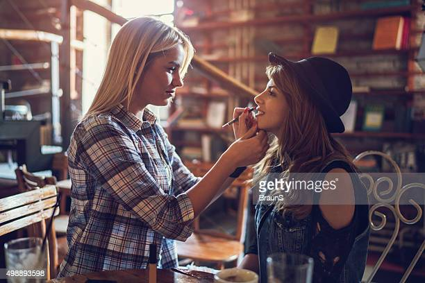 Young woman applying lipstick on her friend's mouth at cafe.