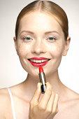 Young woman applying lipstick, portrait