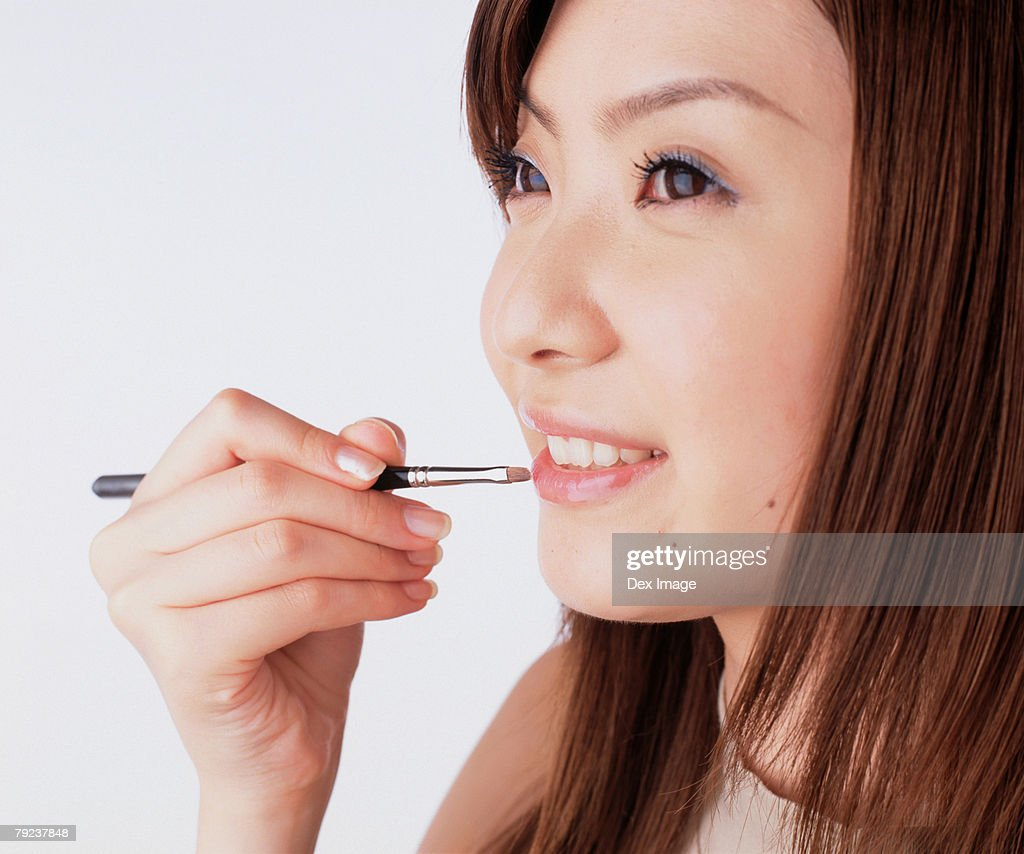 Young woman applying lipstick with a lip brush : Stock Photo
