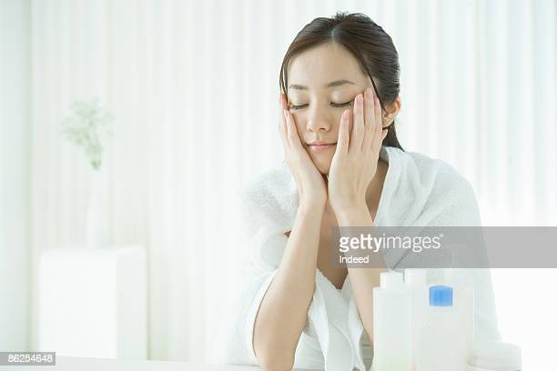 Young woman applying lotion, eyes closed