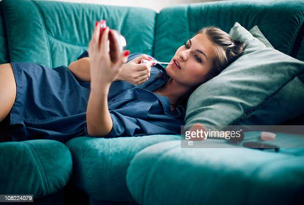 Young Woman Applying Make-Up and Lying on Couch
