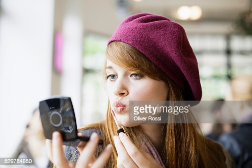 Young woman applying makeup in cafe : Stock Photo