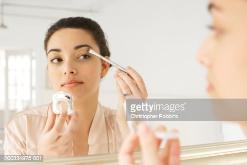 Young woman applying make-up in mirror, using brush, close-up
