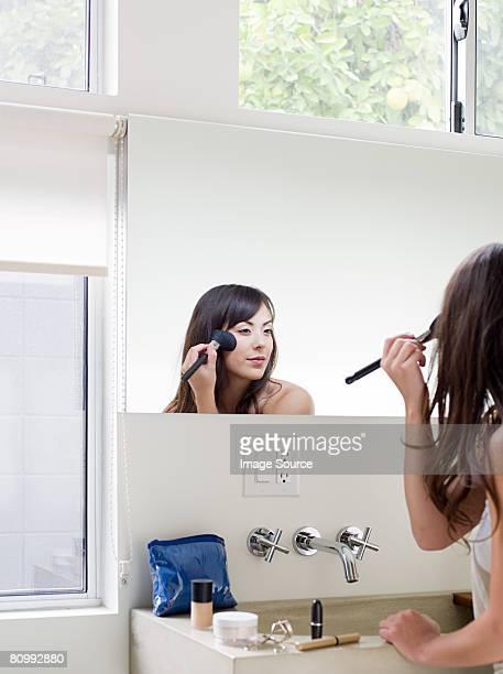 Giovane donna applicando cosmetici