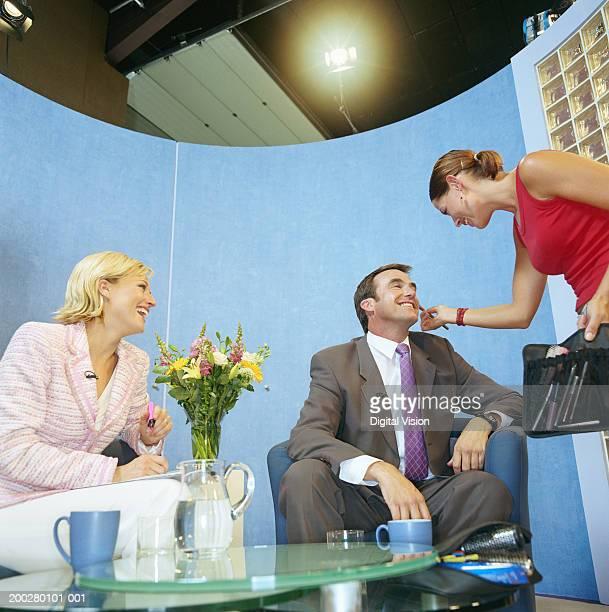 Jeune femme application de maquillage à homme en studio de télévision