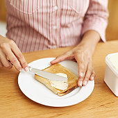Young woman applying margarine to a slice of toast