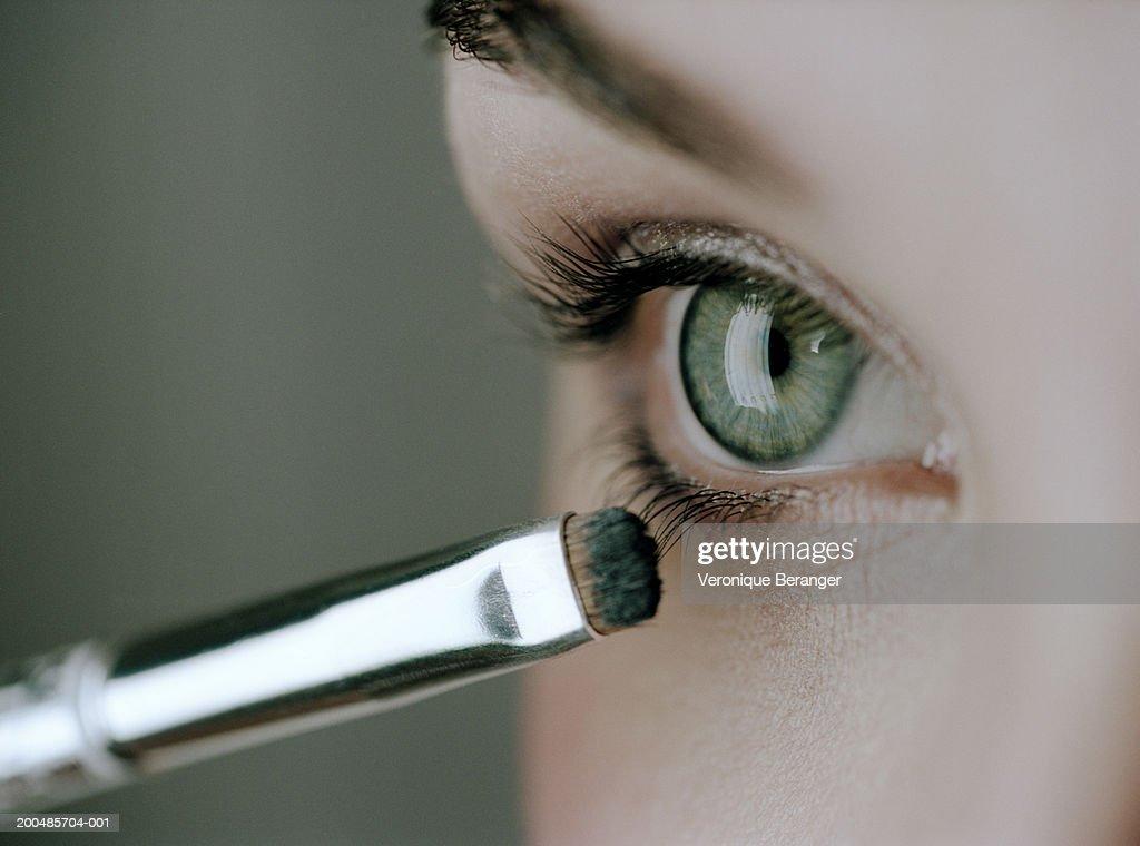 Young woman applying mascara, close-up of eye and eyelashes