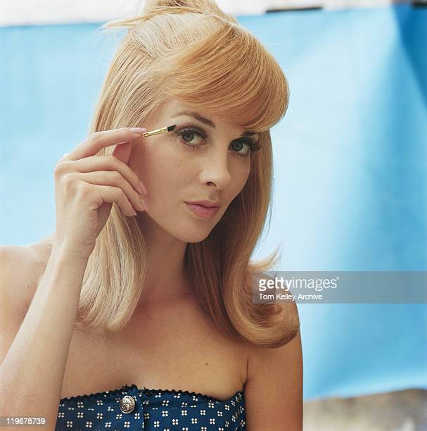 Young woman applying mascara, portrait, close-up