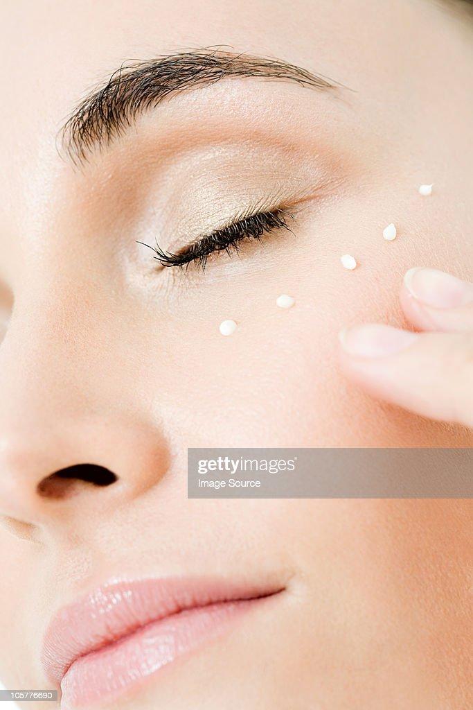Young woman applying moisturiser to her cheek : Stock Photo