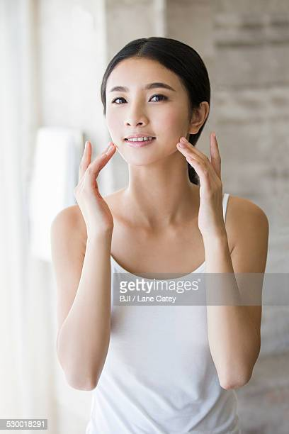 Young woman applying moisturizer