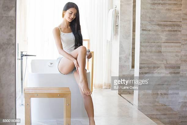 Young woman applying moisturizer to leg