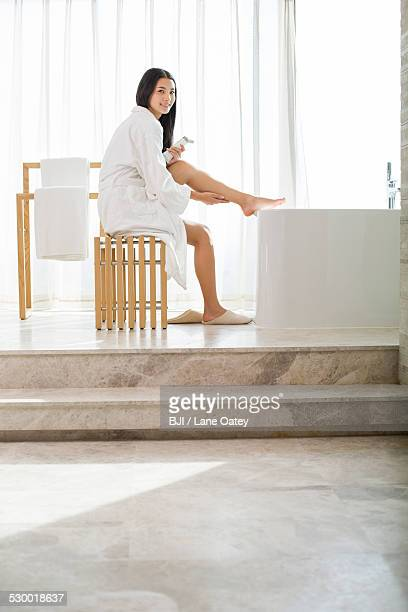 Young woman applying moisturizer to leg