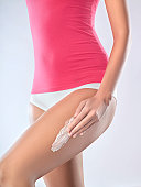 Young woman applying moisturizer to thigh