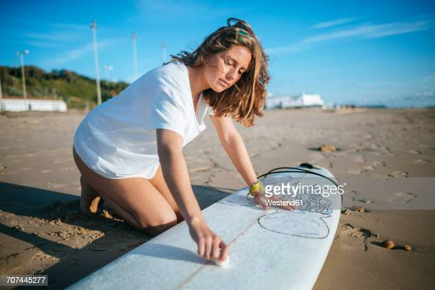 Young woman applying paraffin on surfboard on the beach