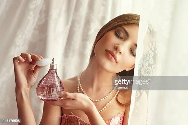 Jeune femme appliquant du parfum